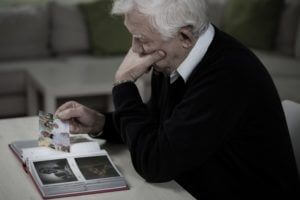 elderly man holding photographs
